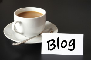 "A cup of coffee with a small sign printed with ""blog."""