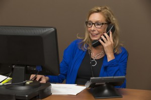 Secretary working at desk and answering phone calls.